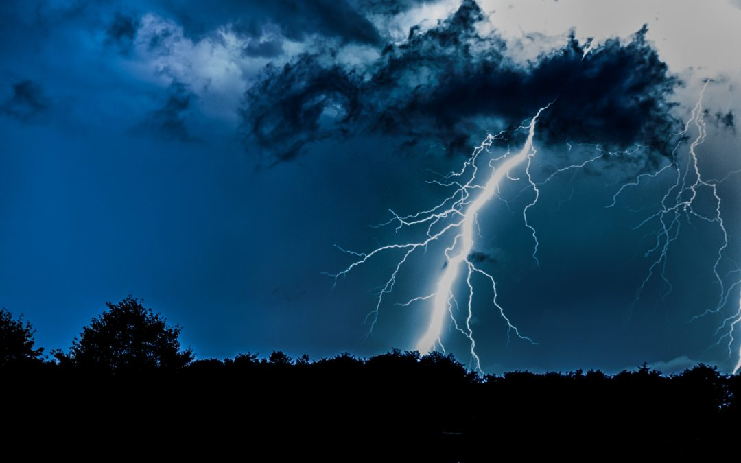 Dark blue sky with scattered clouds and a bright lightning bolt. The outline of trees can be seen.
